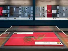 Citi Money Gallery (Room 68, British Museum), shpwing wall cases and in the foreground a creative comparison of modern British forged pound coins and fourth-century copper forgeries or local coinages from Roman Britain.